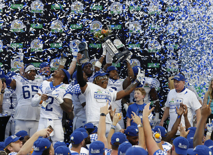 Kentucky players and coach Mark Stoops, right, celebrate after receive the championship trophy following a 27-24 win over Penn State in the Citrus Bowl NCAA college football game Tuesday, Jan. 1, 2019, in Orlando, Fla. (AP Photo/John Raoux)