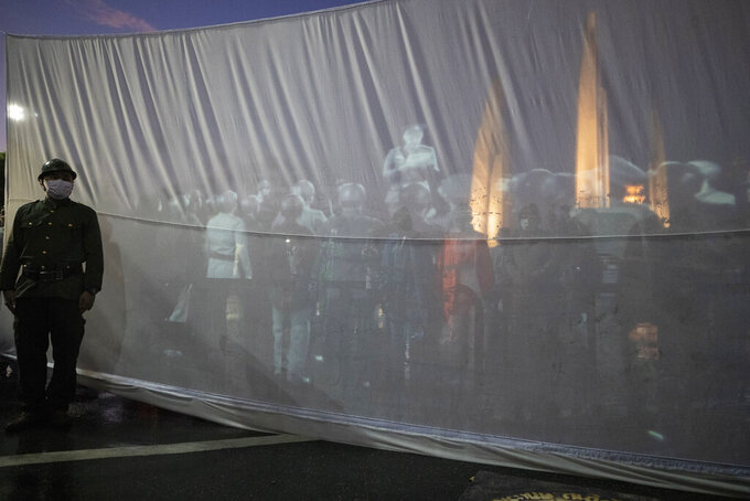 An anti-government activist in soldier costume stands in front of a projection of a video showing a re-enactment of a proclamation in Bangkok, Thailand, Wednesday, June 24, 2020. Thai police and anti-government activists tussled briefly in Bangkok on Wednesday, as authorities tried to stop the pre-dawn commemoration of the anniversary of the day in 1932 when a group of progressive army officers and civil servants proclaimed the end of absolute monarchy and the transition to parliamentary democracy.  (AP Photo/Sakchai Lalit)