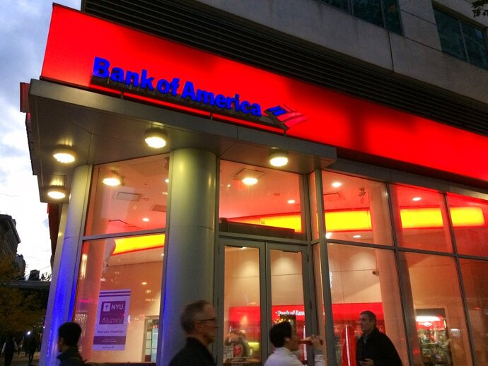 FILE- In this Nov. 6, 2017, file photo, people walk by a branch office of Bank of America in New York. Bank of America Corp. reports earnings Monday, April 16, 2018. (AP Photo/Mark Lennihan, File)