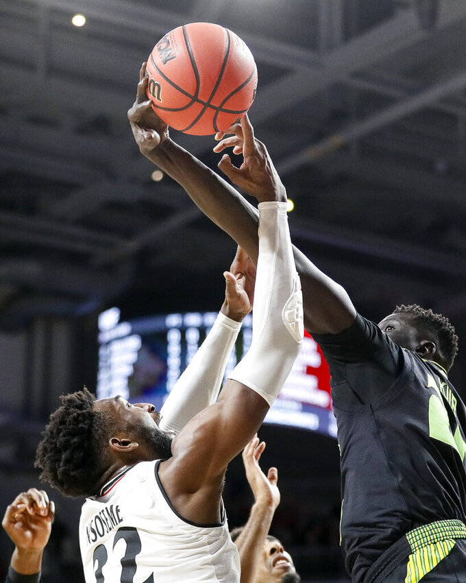 Cincinnati's Eliel Nsoseme, left, and South Florida's Mayan Kiir, right, battle for a rebound in the first half of an NCAA college basketball game, Tuesday, Jan. 15, 2019, in Cincinnati. (AP Photo/John Minchillo)