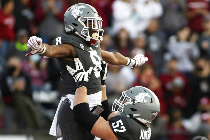 Washington State offensive lineman Jarrett Kingston (52) lifts wide receiver Calvin Jackson Jr. while celebrating Jackson's touchdown during the first half of an NCAA college football game against Stanford, Saturday, Oct. 16, 2021, in Pullman, Wash. (AP Photo/Young Kwak)