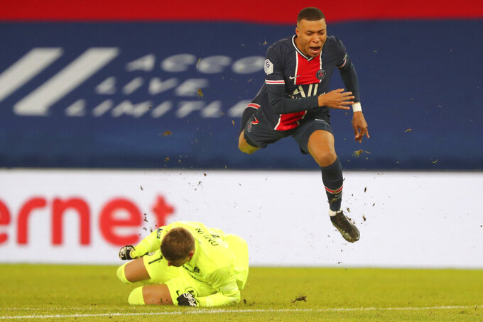 PSG's Kylian Mbappe, right, jumps over Montpellier's goalkeeper Jonas Omlin during the French League One soccer match between Paris Saint-Germain and Montpellier at the Parc des Princes stadium in Paris, France, Friday, Jan.22, 2021. (AP Photo/Thibault Camus)