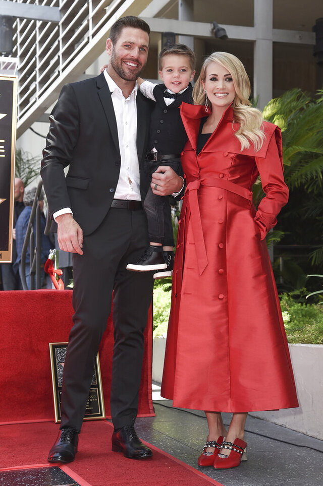 "FILE - In this Sept. 20, 2018 file photo, singer Carrie Underwood poses with her husband Mike Fisher, and their son Isaiah Michael Fisher as they attend a ceremony honoring Underwood with a star on the Hollywood Walk of Fame, in Los Angeles.  Underwood's son provided the adorable vocals on ""Little Drummer Boy,"" one of the 11 tracks on the country superstar's new Christmas album, ""My Gift,"" out Friday, Sept. 25, 2020.  (Photo by Richard Shotwell/Invision/AP, File)"