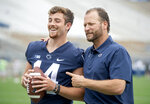 FILE - Penn State quarterback Sean Clifford, left, laughs with offensive coordinator Mike Yurcich as they are asked for a picture together during media day at Beaver Stadium in University Park, Pa., in this Saturday, Aug. 7, 2021, file photo. Penn State has a veteran quarterback in Sean Clifford who is working with his fourth offensive coordinator since he arrived on campus. (Abby Drey/Centre Daily Times via AP, File)