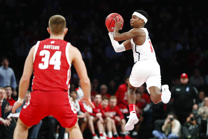 Richmond guard Blake Francis (1) passes as Wisconsin guard Brad Davison (34) watches during the second half of an NCAA college basketball game in the Legends Classic, Monday, Nov. 25, 2019, in New York. Richmond defeated Wisconsin 62-52. (AP Photo/Kathy Willens)