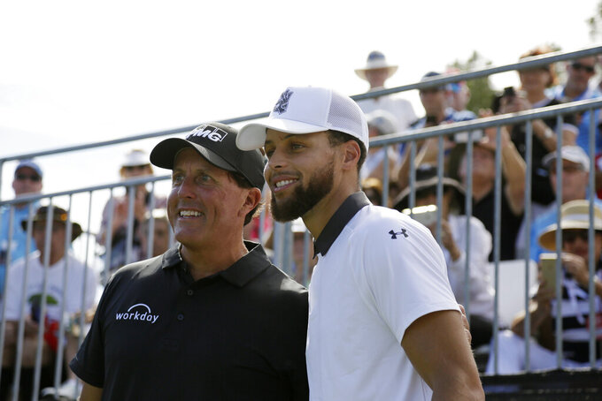 Phil Mickelson, left, and Stephen Curry pose for pictures before hitting from the first tee of the Silverado Resort North Course during the pro-am event of the Safeway Open PGA golf tournament Wednesday, Sept. 25, 2019, in Napa, Calif. (AP Photo/Eric Risberg)
