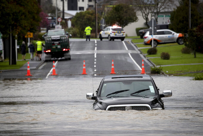 Rising water traps a vehicle in Kumeu, near Auckland, New Zealand, on Aug. 31, 2021, after the region was battered with heavy rain making the area's second wettest day since records began in 1943. New Zealand has endured extreme weather events including severe flooding in some places and dry spells in others. (Dean Purcell/New Zealand Herald via AP)