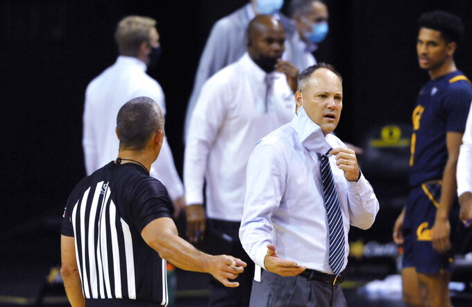 California coach Mark Fox asks a referee to clarify which of his players was called for a foul during the second half against Oregon in an NCAA college basketball game Thursday, Dec. 31, 2020, in Eugene, Ore. (AP Photo/Andy Nelson)