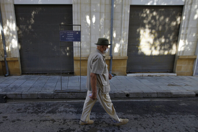 An elderly man wearing protective face mask, crosses from the Geek Cypriot south, to the Turkish occupied north, at Ledra checkpoint in divided capital Nicosia, Cyprus, Friday, June 4, 2021. Ethnically split Cyprus took a key step toward a return to its normal rhythms of life amid the pandemic on Friday when nine crossing points along a United Nations-controlled buffer zone were reopened, enabling ordinary Cypriots to cross the divide. (AP Photo/Petros Karadjias)