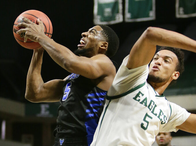 Buffalo guard CJ Massinburg, left, goes to the basket past Eastern Michigan forward Elijah Minnie during the first half of an NCAA college basketball game Friday, Jan. 4, 2019, in Ypsilanti, Mich. (AP Photo/Duane Burleson)