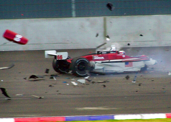 FILE - This Saturday, Sept. 15, 2001 file photo shows Italian driver Alex Zanardi sitting in his car as it breaks up around him after a crash with Canadian driver Alex Tagliani during the CART car race at the Eurospeedway Lausitz in Klettwitz, eastern Germany. Race car driver turned Paralympic champion Alex Zanardi has been seriously injured again. Police tell The Associated Press that Zanardi was transported by helicopter to a hospital in Siena following a road accident near the Tuscan town of Pienza during a national race for Paralympic athletes on handbikes. The 53-year-old Zanardi had both of his legs amputated following a horrific crash during a 2001 CART race in Germany. He was a two-time CART champion. (AP Photo/Eckehard Schulz, File)