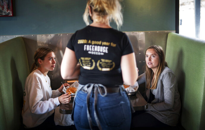 CORRECTS SPELLING OF FIRST NAME TO LINDSEY INSTEAD OF LUNDSEY - FILE - In this Jan. 11, 2021, file photo, Grace Mathre, server at Longfellow Grill, checks on University of St. Thomas students Lindsey Schulz and Maren Daggett in Minneapolis. As the U.S. finds itself in the most lethal phase of the coronavirus outbreak yet, governors and local officials in hard-hit parts of the country are showing little willingness to impose any new restrictions on businesses to stop the spread. (Glen Stubbe/Star Tribune via AP, File)