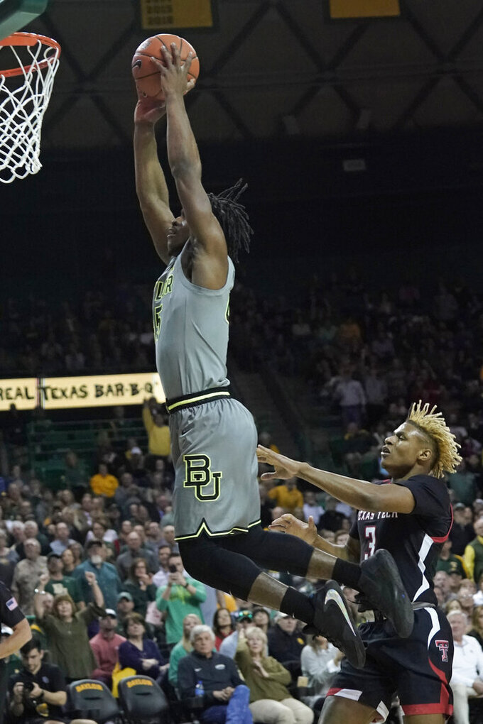 Baylor's Davion Mitchell, left, goes up to dunk past Texas Tech's Jahmi'us Ramsey (3) during the first half of an NCAA college basketball game in Waco, Texas, Monday, March 2, 2020. (AP Photo/Chuck Burton)