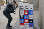 A voter makes sure his ballot falls into the ballot drop box outside the Boston Public Library, Monday, Oct. 26, 2020, in Boston. Massachusetts election officials say a fire was set in the ballot drop box Sunday, holding more than 120 ballots in what appears to have been a