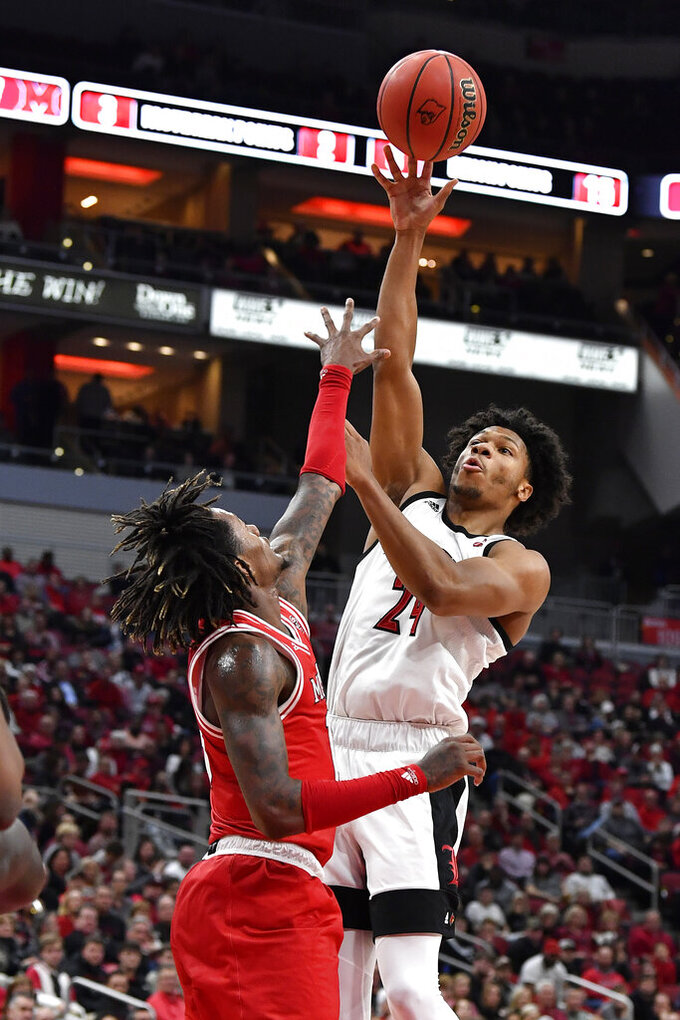 Louisville forward Dwayne Sutton (24) shoots over Miami (Ohio) forward Dalonte Brown (13) during the second half of an NCAA college basketball game in Louisville, Ky., Wednesday, Dec. 18, 2019. Louisville won 70-46. (AP Photo/Timothy D. Easley)