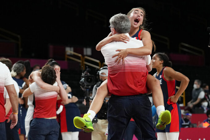 France's Marine Fauthoux (4) leaps into the arms of a staff member as they celebrate the team's win over Serbia in a women's basketball bronze medal game at the 2020 Summer Olympics, Saturday, Aug. 7, 2021, in Saitama, Japan. (AP Photo/Eric Gay)
