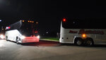 Three buses arrive at the Pennsylvania International Academy dorms Tuesday night, April 13, 2021, in Summit Township, Pa., carrying the a group of migrant children, 146 girls ages 7-12, detained at the U.S.-Mexico border. The girls were flown to Erie International Airport then transported to the facility to receive temporary shelter. (Greg Wohlford/Erie Times-News via AP)