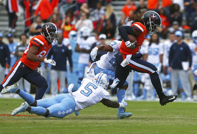 Virginia's quarterback Bryce Perkins (3) is tackled by two North Carolina defenders on a run during the first half of an NCAA college football game Saturday, Oct. 27, 2018, in Charlottesville, Va. (Zack Wajsgras /The Daily Progress via AP)
