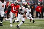 Maryland quarterback Tyrrell Pigrome, right, tries to scramble away from Ohio State defensive end Tyreke Smith during the first half of an NCAA college football game, Saturday, Nov. 9, 2019, in Columbus, Ohio. (AP Photo/Jay LaPrete)