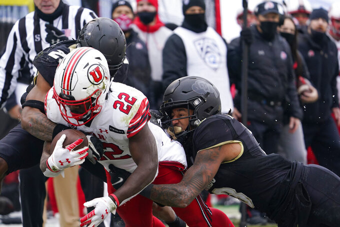 Utah running back Ty Jordan, front left, is pulled down short of the goal line by Colorado safety Derrion Rakestraw, front right, and cornerback Mekhi Blackmon in the second half of an NCAA college football game Saturday, Dec. 12, 2020, in Boulder, Colo. Utah won 38-21. (AP Photo/David Zalubowski)