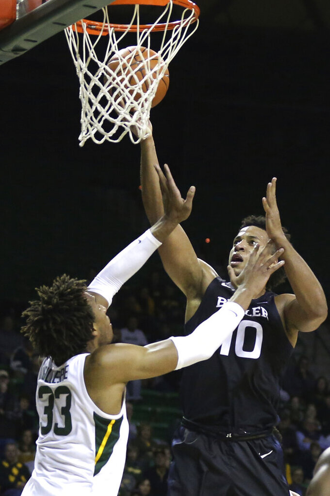Butler forward Bryce Nze, right, shoots over Baylor forward Freddie Gillespie in the first half of an NCAA college basketball game, Tuesday, Dec. 10, 2019, in Waco, Texas. (AP Photo/Rod Aydelotte)