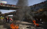 FILE - In this Aug. 10, 2020 file photo, demonstrators burn tires to protest the postponement of the upcoming presidential election in El Alto, Bolivia. Citing the ongoing new coronavirus pandemic, the nation's highest electoral authority delayed presidential elections from Sept. 6 to Oct. 18, the third time the vote has been delayed. (AP Photo/Juan Karita, File)
