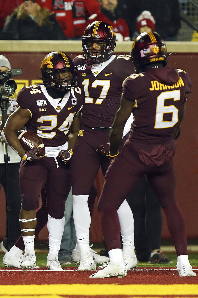 Minnesota running back Mohamed Ibrahim (24) celebrates with teammates Seth Green (17) and Tyler Johnson (6) after scoring a touchdown against Nebraska during an NCAA college football game Saturday, Oct. 12, 2019, in Minneapolis. (AP Photo/Stacy Bengs)