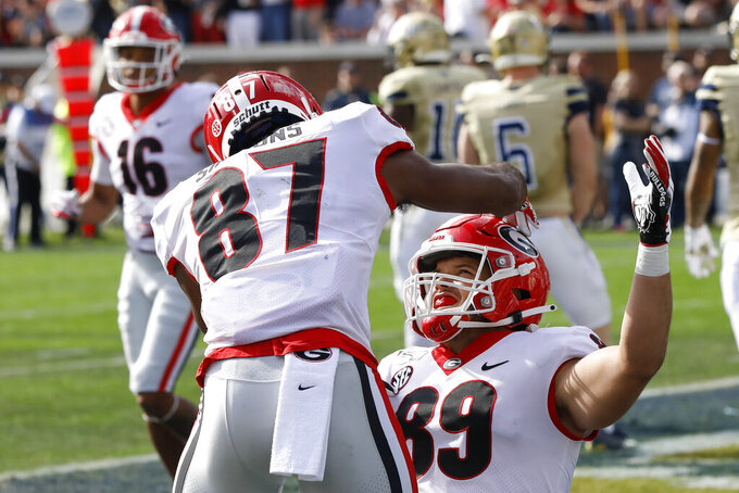Georgia tight end Charlie Woerner (89) celebrates with Tyler Simmons (87) after scoring a touchdown against Georgia Tech during the first half of an NCAA college football game Saturday, Nov. 30, 2019, in Atlanta. (Joshua L. Jones/Athens Banner-Herald via AP)