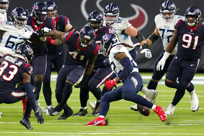 Tennessee Titans running back Derrick Henry, center, fumbles the ball as Houston Texans inside linebacker Zach Cunningham (41) defends during the second half of an NFL football game Sunday, Jan. 3, 2021, in Houston. The Texans recovered the fumble. (AP Photo/Sam Craft)