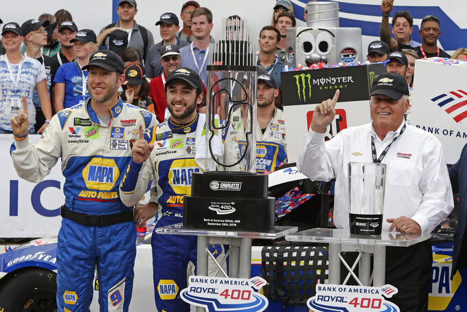 Chase Elliott, center, car owner Rick Hendrick, right, and crew chief Alan Gustafson celebrate in victory lane after Elliot won the NASCAR Cup Series auto race at Charlotte Motor Speedway in Concord, N.C., Sunday, Sept. 29, 2019. (AP Photo/Wesley Broome)