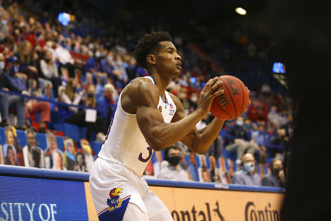 Kansas guard Ochai Agbaji lines up a 3-pointer against West Virginia during the first half of an NCAA college basketball game Tuesday, Dec. 22, 2020, in Lawrence, Kan. (Evert Nelson/The Topeka Capital-Journal via AP)