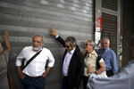 Pensioners rattle the shutters of the main entrance of the Labor ministry during a protest in central Athens, on Wednesday, May 16, 2018. The government has repeatedly cut pensions as part of the country's three international bailouts. More cuts are planned in 2019. (AP Photo/Petros Giannakouris)