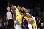 Golden State Warriors' D'Angelo Russell, right, dribbles around Los Angeles Lakers' Avery Bradley, center, on a screen from Draymond Green during the second half of an NBA basketball game Wednesday, Nov. 13, 2019, in Los Angeles. (AP Photo/Marcio Jose Sanchez)