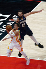 Atlanta Hawks guard Trae Young (11) goes to the basket as New Orleans Pelicans center Steven Adams (12) defends in the first half of an NBA basketball game Tuesday, April 6, 2021, in Atlanta. (AP Photo/John Bazemore)
