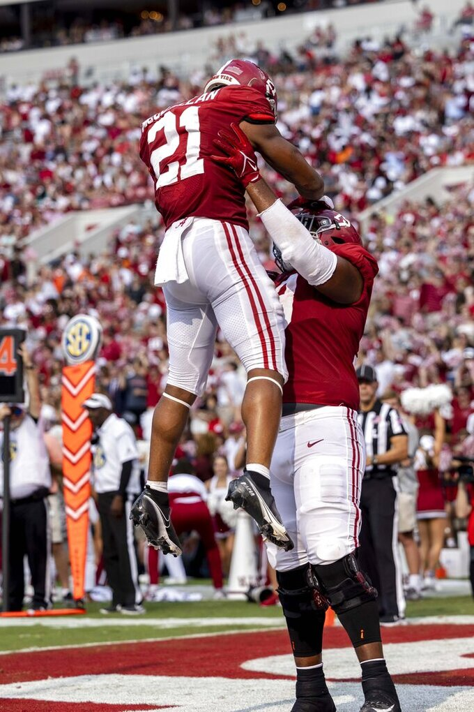 Alabama offensive lineman Chris Owens (79) gives running back Jase McClellan (21) a boost as they celebrate McClellan's touchdown against Mercer during the first half of an NCAA college football game, Saturday, Sept. 11, 2021, in Tuscaloosa, Ala. (AP Photo/Vasha Hunt)