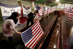 In this Saturday, Feb. 8, 2020 photo, workers hang U.S. flags and Israeli flags with a slogan in Persian which reads,