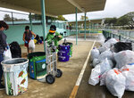 In this March 18, 2021, photo provided by Maria Price, Genshu Price, right, and other volunteers at S.W. King Intermediate School in Kāne'ohe, Hawaii, sort cans and bottles for Bottles4College, a recycling project he started that raises money for students' college tuition. (Bottles4College via AP)