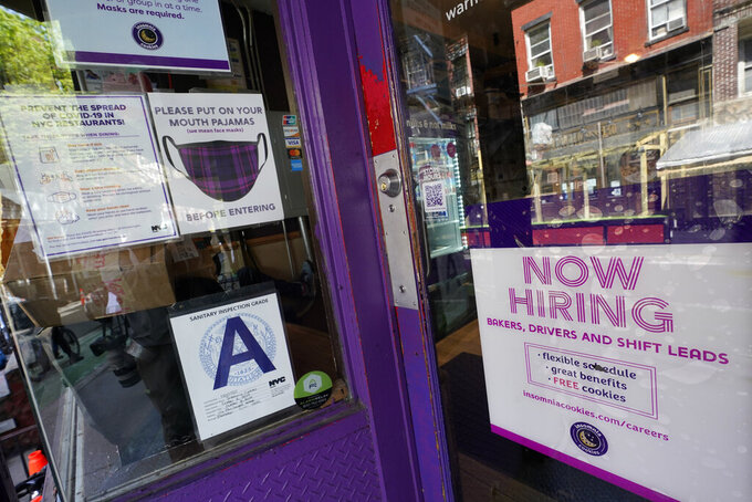 FILE - In this May 4, 2021 file photo, a signs announcing they are hiring hangs in the window of a restaurant in the Greenwich Village neighborhood of Manhattan in New York.   The economic recovery's seemingly open road ahead could get a little bumpy from here.  The employment market, a key factor in a full recovery from the pandemic, has been stubbornly lagging behind.  (AP Photo/Mary Altaffer, File)