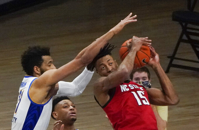 North Carolina State's Manny Bates (15) comes down with a rebound, with less than 3 seconds left, next to Pittsburgh's Terrell Brown during the second half of an NCAA college basketball game Wednesday, Feb. 17, 2021, in Pittsburgh. N.C. State won 74-73. (AP Photo/Keith Srakocic)