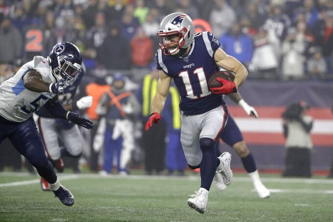 New England Patriots wide receiver Julian Edelman carries the ball as Tennessee Titans linebacker David Long, left, chases in the second half of an NFL wild-card playoff football game, Saturday, Jan. 4, 2020, in Foxborough, Mass. (AP Photo/Steven Senne)
