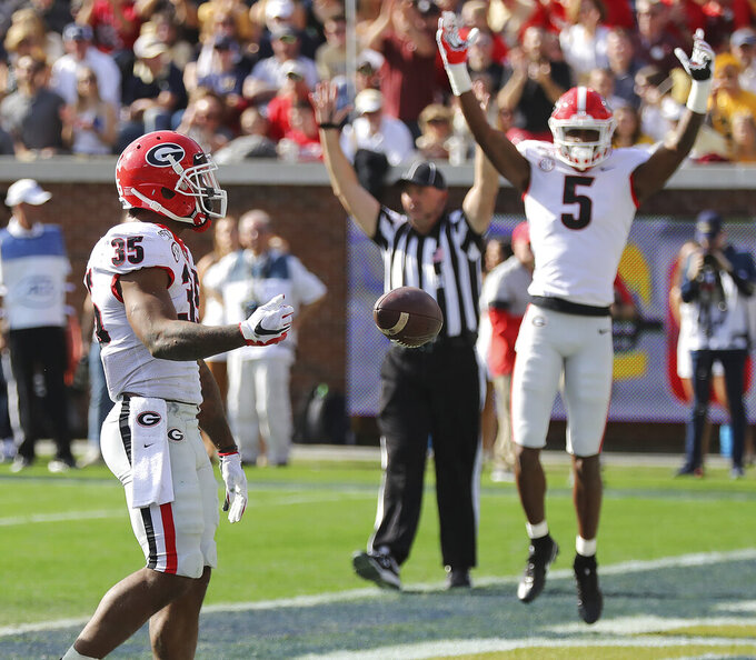 Georgia tailback Brian Herrien scores while teammate Matt Landers and the official signal the touchdown for the early 10-0 lead over Georgia Tech during the first quarter in a NCAA college football game on Saturday, November 30, 2019, in Atlanta. (Curtis Compton/Atlanta Journal-Constitution via AP)