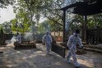 Indian health workers in protective suit return after bringing the body of a person who died of COVID-19 for cremation in Gauhati, India, Tuesday, April 27, 2021. The COVID-19 death toll in India has topped 200,000 as the country endures its darkest chapter of the pandemic yet. (AP Photo/Anupam Nath)