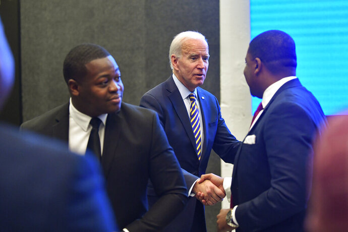 Former Vice President and 2020 Democratic presidential candidate Joe Biden is greeted by Fayetteville (NC) mayor Mitch Colvin, right, after talking to Talladega (Ala.) mayor Timothy Ragland, left, as he visits with an assembly of Southern black mayors Thursday, Nov. 21, 2019 in Atlanta. (AP Photo/John Amis)
