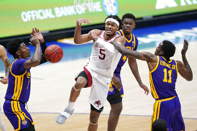 Arkansas' Moses Moody (5) loses the ball as he drives against LSU's Josh LeBlanc Sr. (11) in the second half of an NCAA college basketball game in the Southeastern Conference Tournament Saturday, March 13, 2021, in Nashville, Tenn. (AP Photo/Mark Humphrey)
