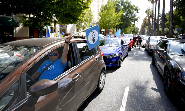 FILE - In this Aug. 28, 2019, file photo, dozens of supporters of a measure to limit when companies can label workers as independent contractors circle the Capitol during a rally in Sacramento, Calif. Ride-share company Uber and on-demand meal delivery service Postmates sued Monday, Dec. 30, 2019, to block a broad new California law aimed at giving wage and benefit protections to people who work as independent contractors. The lawsuit filed in U.S. court in Los Angeles argues that the law set to take effect Wednesday, Jan. 1, 2020, violates federal and state constitutional guarantees of equal protection and due process. (AP Photo/Rich Pedroncelli, File)