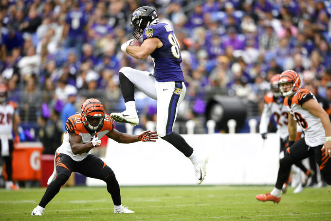 Baltimore Ravens tight end Mark Andrews, right, begins to leap over Cincinnati Bengals defensive back Brandon Wilson (40) during the first half of a NFL football game Sunday, Oct. 13, 2019, in Baltimore. Andrews fumbled the ball and the Bengals recovered. (AP Photo/Nick Wass)