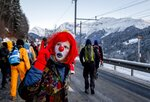 A man dressed as a clown is part of hundreds of climate protesters who are on a three-day  protest march from Landquart to Davos pass the city of Klosters, Switzerland, Monday, Jan. 20, 2020. The World Economic Forum will start on Tuesday. (AP Photo/Michael Probst)