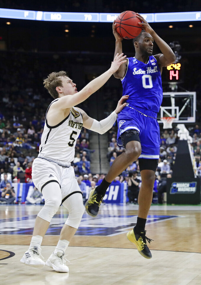 Seton Hall's Quincy McKnight (0) passes the ball as Wofford's Storm Murphy (5) defends during the first half of a first-round game in the NCAA men's college basketball tournament in Jacksonville, Fla., Thursday, March 21, 2019. (AP Photo/John Raoux)