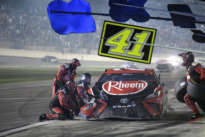 Crew members work on the car driven by Christopher Bell (20) on pit road during a NASCAR Cup Series auto race at Daytona International Speedway, Saturday, Aug. 28, 2021, in Daytona Beach, Fla. (AP Photo/Phelan M. Ebenhack)
