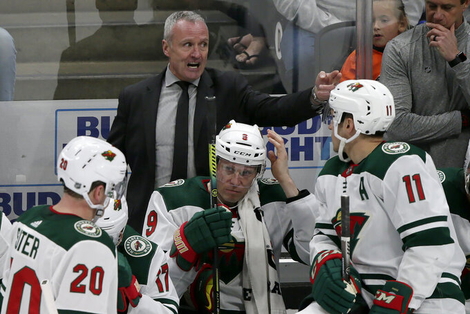 FILE - In this Sunday, March 8, 2020, file photo, Minnesota Wild interim head coach Dean Evason, above center, directs players behind the bench during the overtime period of an NHL hockey game against the Anaheim Ducks in Anaheim, Calif. The Minnesota Wild made Dean Evason their full-time head coach on Monday, July 13, 2020,   signing him to a two-year contract extension at the commencement of training camp for the restarted NHL season.(AP Photo/Alex Gallardo, File)